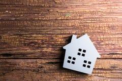 Деревянная игрушка дома на деревянной предпосылке с космосом экземпляра Реальное Estat Стоковая Фотография