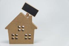 Деревянная игрушка дома и малая черная доска с белой предпосылкой и селективным фокусом Стоковое Изображение RF