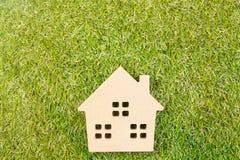 Деревянная игрушка дома на земной зеленой траве с космосом экземпляра Реальное esta Стоковые Фотографии RF
