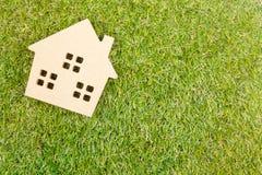 Деревянная игрушка дома на земной зеленой траве с космосом экземпляра Реальное esta Стоковая Фотография