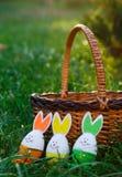 Деревянная корзина с лож апельсина, желтых и зеленых яя на траве весны зеленой на солнечном свете Счастливая пасха! Украшение, ох стоковая фотография rf