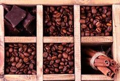 Деревянная коробка с комплектом кофейных зерен, темного шоколада и циннамона Стоковое фото RF