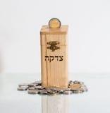 Деревянная коробка Tzedakah, переводя призрение текста Стоковое Фото