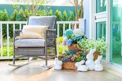 Деревянная кресло-качалка и цветки в корзине на деревянном f Стоковые Изображения