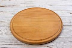 Деревянная круглая пустая доска для пиццы на деревянной предпосылке таблицы, взгляд сверху Модель-макет для меню, рецепта или люб Стоковые Изображения