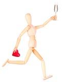 Деревянная кукла при шампанское держа красное сердце Стоковые Фотографии RF