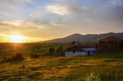 Деревянная лачуга, голубые небеса, и зеленые поля с живыми облаками оно рассвет, стоковые фотографии rf