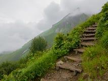 Деревянная лестница на пеший-пути с облаками и туманом стоковая фотография rf