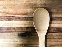 Деревянная ложка на деревянной разделочной доске Стоковое Изображение