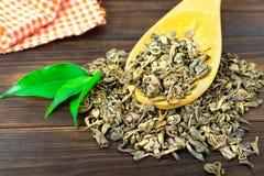 Деревянная ложка сухого чая с листьями зеленого чая на darkbackground стоковое фото
