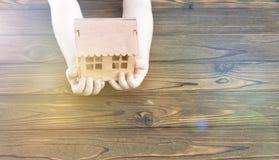 Деревянная модель дома в руках ребенка на деревянной предпосылке стоковые изображения
