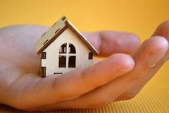 Деревянная модель дома игрушки в руке человека на желтом виде спереди предпосылки стоковое изображение