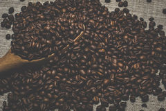Деревянная ложка и зажаренные в духовке кофейные зерна, разбросанные на грубую мешковину Стоковые Фото
