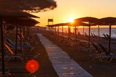 Деревянная дорожка на пляже среди loungers солнца и зонтиков на заходе солнца, Греции соломы, Родоса Стоковая Фотография