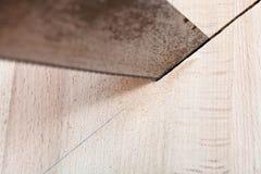 Деревянная доска отрезана с hacksaw Стоковая Фотография