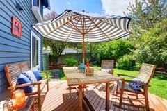 Деревянная палуба выхода в саде задворк голубого дома siding Стоковые Фотографии RF