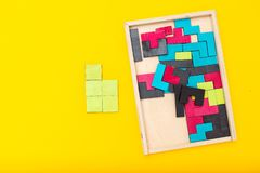 Деревянная пестротканая головоломка на желтой предпосылке Плоское положение стоковое изображение rf