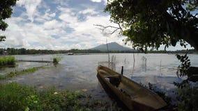 Деревянная поставленная на якорь шлюпка строки, плавающ на загрязнянное озеро сток-видео