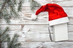 Деревянная предпосылка бело Карточка зимы Его шляпа ` s Санты разветвляет зеленый цвет ели xmas вектора иллюстрации карточки Пись Стоковая Фотография