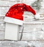 Деревянная предпосылка бело Карточка зимы Его шляпа ` s Санты разветвляет зеленый цвет ели xmas вектора иллюстрации карточки Пись Стоковое фото RF