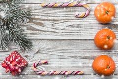 Деревянная предпосылка Белые белизны Зеленый цвет ветви ели Оранжевый конфета цветастая Карточка зимы, праздничный подарок Стоковые Фотографии RF