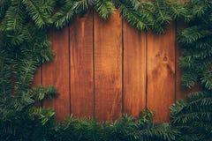 Деревянная предпосылка рождества обрамленная ветвями ели стоковая фотография