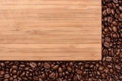Деревянная предпосылка вокруг краев взбрызнутых с зажаренным в духовке кофе зерна, космосом для текста Стоковое Изображение
