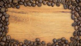 Деревянная предпосылка обрамленная зажаренными в духовке кофейными зернами Стоковые Фотографии RF