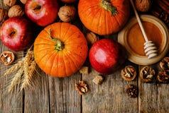 Деревянная предпосылка с тыквой, яблоками, пшеницей, медом и гайками Стоковое фото RF