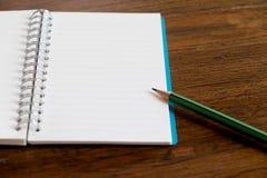 Деревянная предпосылка таблицы с карандашем бумаги примечания Стоковое фото RF