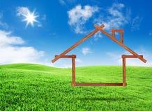Деревянная принципиальная схема иконы дома на поле зеленой травы Стоковые Изображения