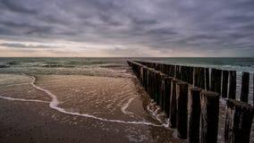 Деревянная пристань во время драматической пасмурной погоды на пляже в Vlissingen, Зеландии, Голландии, Нидерландах Стоковое фото RF