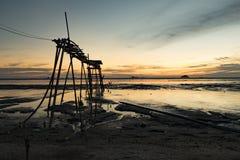 Деревянная пристань над волшебным светом во время предпосылки захода солнца тинный пляж и мягкое облако Стоковая Фотография RF