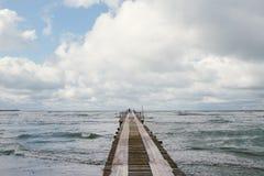 Деревянная пристань на seashore с бурным морем Стоковые Изображения RF
