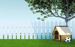Деревянная псарня собаки под тенью дерева на луге зеленой травы с загородкой футбольного мяча и белых деревянной Стоковое фото RF