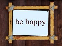 Деревянная рамка на деревянной предпосылке Надпись, счастлива Стоковая Фотография