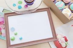 Деревянная рамка с белым листом вокруг меренги и пирожного с пестротканой сливк, масштабом кухни, кассетой Стоковое Изображение