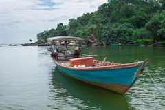 деревянная рыбацкая лодка в голубых и зеленых водах Камбоджи Стоковое фото RF