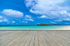 Деревянная серая пристань на совершенном пляже в солнечном дне с голубым небом Стоковое фото RF