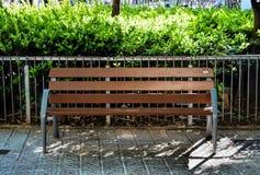 Деревянная скамья, зеленые растения на предпосылке Стоковые Фото