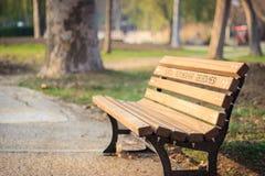 Деревянная скамья около дороги в парке Стоковые Фотографии RF