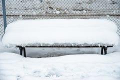 Деревянная скамья покрытая с снегом в парке ждет товарищество стоковые изображения