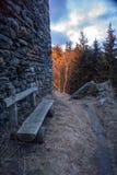 Деревянная скамья рядом с каменной стеной Стоковое фото RF