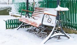 Деревянная скамья совсем покрыта со снегом стоковое фото rf