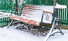 Деревянная скамья совсем покрыта со снегом стоковое изображение