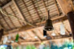 Деревянная скульптура сделанная сырцового колокола кольца ofBronze корней повиснула под деревянной крышей камбоджийский вал Стоковые Фото