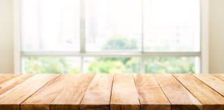 Деревянная столешница на нерезкости стекла окна и абстрактного зеленого сада стоковое изображение