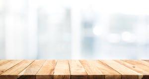 Деревянная столешница на предпосылке здания стены стеклянного окна нерезкости