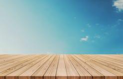 Деревянная столешница на небе и белизне градиента голубом заволакивает предпосылка также использованный для дисплея или монтажа в Стоковое Изображение
