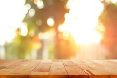 Деревянная столешница на сияющей предпосылке bokeh солнечного света Стоковые Изображения